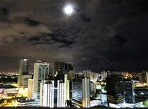 The moon rises above buildings in Salvador, Brazil December 4, 2012. REUTERS/Gary Hershorn
