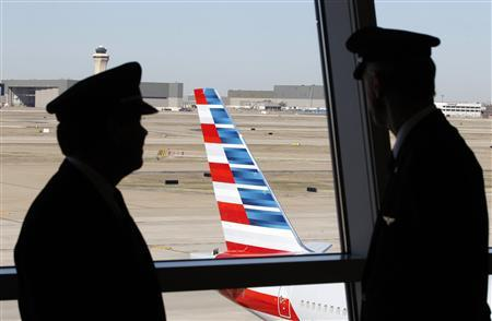 Pilots talk as they look at the tail of an American Airlines aircraft following the announcement of the planned merger of American Airlines and US Airways, at Dallas-Ft Worth International Airport February 14, 2013. REUTERS/Mike Stone