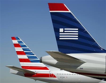 The tail sections of American Airlines (L) and US Airways aircraft are on the ramp at Dallas-Ft Worth International Airport February 14, 2013. REUTERS/Mike Stone