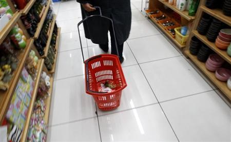 A woman pulls a shopping cart inside a shop where all products are sold at the price of one euro in Athens December 8, 2011. REUTERS/Yiorgos Karahalis