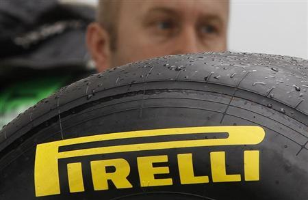 A Force India Formula One technician is seen behind a tyre of the new provider Pirelli ahead of this weekend's Australian Grand Prix in Melbourne March 24, 2011. REUTERS/Daniel Munoz