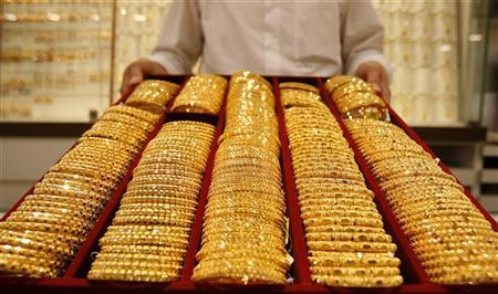 A shop attendant displays a tray of gold bangles for the camera at a jewellery story in Singapore September 18, 2008. REUTERS/Vivek Prakash/Files