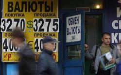 Люди проходят мимо пункта обмена валюты в Москве 31 мая 2012 года. Рубль балансирует в пятницу к бивалютной корзине на границе начала интервенционных покупок центробанком, динамика определяется корпоративными денежными потоками на покупку и продажу валюты в зависимости от динамики пары доллар/рубль и в условиях начавшегося налогового периода. REUTERS/Maxim Shemetov