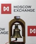 Колокольчик звенит в начале торговой сессии на фоне логотипа Московской биржи 15 февраля 2013 года. Московская биржа привлечет $498 млн в ходе IPO. REUTERS/Maxim Shemetov
