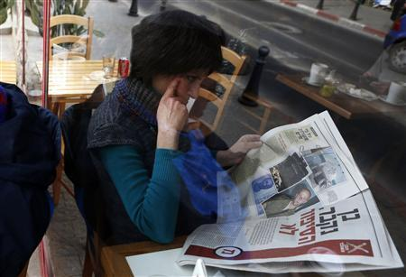 A woman is seen through a coffee shop window as she reads an article about Ben Zygier in an Yedioth Ahronoth newspaper in Jerusalem February 15, 2013. Zygier, the Australian immigrant reported to have been recruited by Israel's Mossad spy agency, was charged with grave crimes before he committed suicide in an Israeli jail, one of his lawyers said on Thursday. REUTERS/Baz Ratner