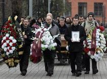 Friends and relatives take part in the funeral ceremony of Sergei Magnitsky at a cemetery in Moscow November 20, 2009. REUTERS/Mikhail Voskresensky