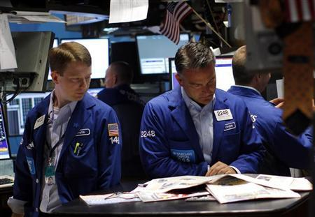 Traders read the morning papers on the main trading floor of the New York Stock Exchange July 29, 2011. REUTERS/Mike Segar