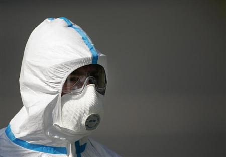 A worker in a bio-hazard suit poses to the media at the entry of a poultry farm in Wachenroth, southern Germany in this file photo taken August 26, 2007. REUTERS/Hannibal Hanschke