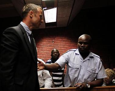 South African 'Blade Runner' Oscar Pistorius (C) is escorted by police during his court appearance in Pretoria February 15, 2013. REUTERS/Siphiwe Sibeko