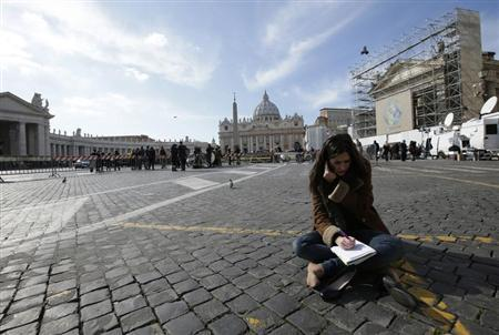 A media correspondent sits on the ground in Rome, as Saint Peter's Basilica at the Vatican is seen in the background, February 13, 2013. REUTERS/Max Rossi