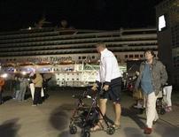 """Passageiros deixam o navio Carnival Triumph após atracarem no porto de Mobile, no Alabama. O navio de passageiros, que passou mais de quatro dias sem energia no Golfo do México, chegou rebocado ao porto de Mobile na noite de quinta-feira, e os ocupantes festejaram o final de uma viagem """"infernal"""", marcada por banheiros transbordando e pelo mau cheiro nas cabines. 14/02/2013 REUTERS/ Lyle Ratliff"""