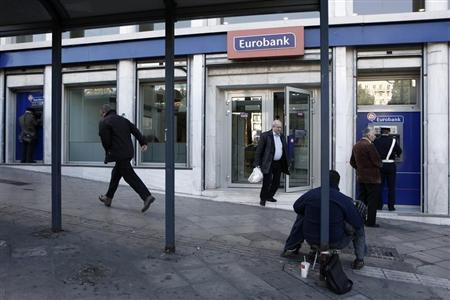 A beggar sits outside a Eurobank branch in Athens December 10, 2012. REUTERS/Yorgos Karahalis