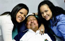 Venezuela's President Hugo Chavez smiles in between his daughters, Rosa Virginia (R) and Maria while recovering from cancer surgery in Havana in this photograph released by the Ministry of Information on February 15, 2013. REUTERS/Ministry of Information/Handout