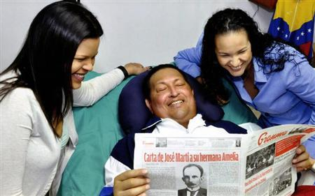 Venezuela's President Hugo Chavez holds a copy of the Cuban newspaper Granma as his daughters, Rosa Virginia (R) and Maria watch while recovering from cancer surgery in Havana in this photograph released by the Ministry of Information on February 15, 2013. Venezuela's government published the first pictures of cancer-stricken Chavez since his operation in Cuba more than two months ago, showing him smiling while lying in bed reading a newspaper, flanked by his two daughters. The 58-year-old socialist leader had not been seen in public since the Dec. 11 surgery, his fourth operation in less than 18 months. The government said the photos were taken in Havana on February 14, 2013. REUTERS/Ministry of Information/Handout