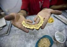 A worker holds a gold necklace at a gold workshop in the city of Isfahan, 414 km (259 miles) south of Tehran May 3, 2007. REUTERS/Morteza Nikoubazl