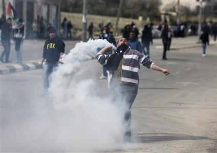 A Palestinian protester throws back a tear gas canister fired by Israeli border policemen during clashes outside Israel's Ofer prison near the West Bank city of Ramallah February 15, 2013. REUTERS/Mohamad Torokman