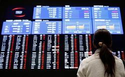 El mercado bursátil español cerró la sesión del viernes en un descenso superior al uno por ciento y en los niveles más bajos del día arrastrada por la evolución de los valores de mayor ponderación y en espera de la reunión del G-20 que se celebra este fin de semana en Moscú. En laimagen, una mujer mira pantallas electrónicas mostran el índice bursátil en la bolsa de Toko, el 6 de febrero de 2013REUTERS/Toru Hanai.