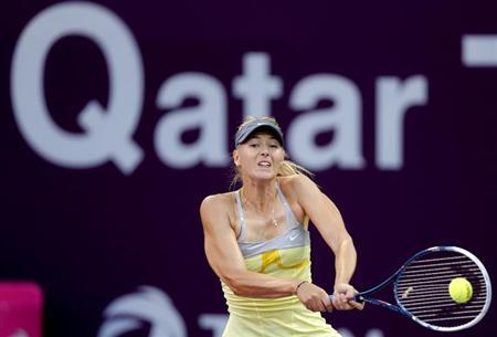 Maria Sharapova of Russia returns the ball to Samantha Stosur of Australia during their women's quarter-final match at the Qatar Open tennis tournament in Doha February 15, 2013. REUTERS/Fadi Al-Assaad