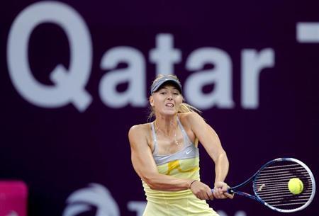Maria Sharapova of Russia returns the ball to Samantha Stosur of Australia during their women's quarter-final match at the Qatar Open tennis tournament in Doha February 15, 2013. REUTERS/Fadi Al-Assaad