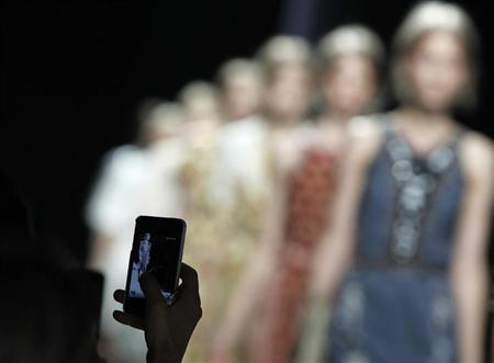 A woman uses her mobile phone to shoot a video during the Bottega Veneta Spring/Summer 2013 collection at Milan Fashion Week September 22, 2012. REUTERS/Alessandro Garofalo