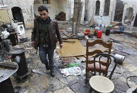 A Free Syrian Army fighter walks among debris in a house damaged by fighting between the Free Syrian Army and forces loyal to Syria's President Bashar al-Assad, in the old city of Aleppo February 15, 2013. REUTERS/Muzaffar Salman