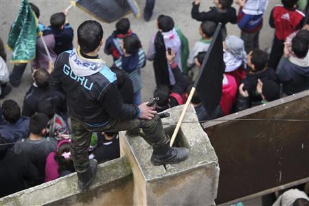 A member of the Free Syrian Army watches a demonstration against Syria's President Bashar al-Assad in Bustan al Qasr district in Aleppo February 15, 2013. REUTERS/Muzaffar Salman