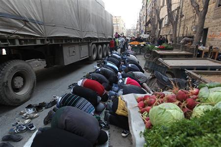 People pray along a street before a protest against Syria's President Bashar al-Assad in Bustan al Qasr district in Aleppo February 15, 2013. REUTERS/Muzaffar Salman