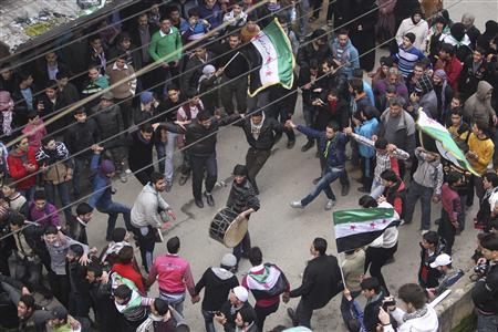 Demonstrators chant slogans as they dance and wave Syrian opposition flags during a protest against President Bashar al-Assad in the Bustan al-Qasr district in Aleppo February 15, 2013. REUTERS/Muzaffar Salman