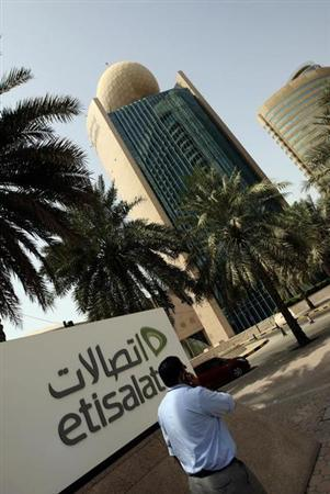 A man talks on his mobile phone as he walks past the Etisalat Telecommunications building in Dubai August 2, 2010. REUTERS/Mosab Omar