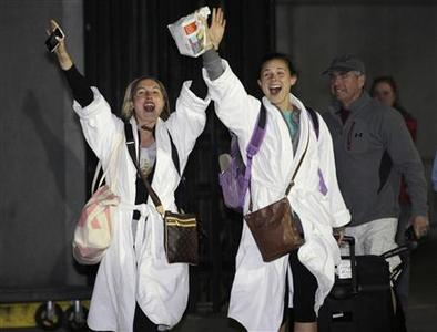 Passengers cheer after disembarking from the Carnival Triumph cruise ship after reaching the port of Mobile, Alabama, February 14, 2013. REUTERS/ Lyle Ratliff