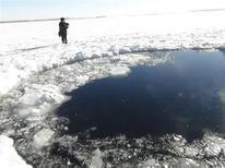 Un meteorito cruzó el cielo y explotó sobre el centro de Rusia el viernes, enviando bolas de fuego a la Tierra que destrozaron numerosas ventanas y dañar edificios, causando heridas a más de 1.000 personas. En la imagen del 15 de febrero se puede ver a un policía junto al agujero en el hielo que según el Ministerio del Interior fue causado por uno de los fragmentos del meteorito en el llago Chebarkul, a unos 80 kilómetros al oeste de Chelyabinsk. REUTERS/Chelyabinsk region Interior Ministry/Handout AS A SERVICE TO CLIENTS - RTR3DU76