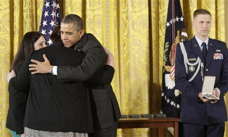U.S. President Barack Obama (3rd L) hugs Sarah Davino (L) and Mary Davino (2nd L), as he awards the Presidential Citizens Medal posthumously to their family member Rachel Davino, a teacher who gave her life in the Sandy Hook school shooting in Connecticut in December, in the East Room at the White House in Washington, February 15, 2013. REUTERS/Jonathan Ernst