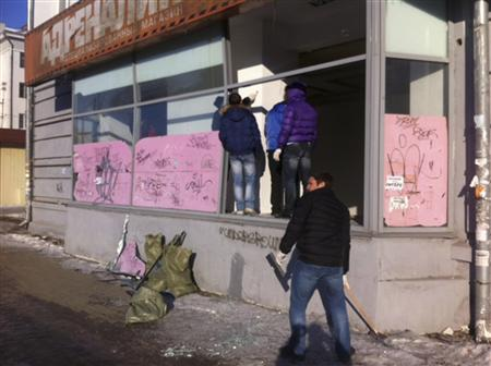 People look at damage to a shop following sightings of falling objects in the sky in the Urals city of Chelyabinsk February 15, 2013. REUTERS/Andrei Kuzmin