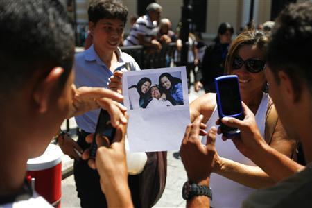 Supporters of Venezuelan President Hugo Chavez take pictures of a copy of a photograph of Chavez released by the Ministry of Information, during a gathering at Plaza Bolivar in Caracas February 15, 2013. REUTERS/Carlos Garcia Rawlins