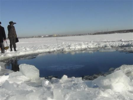Russian police work near an ice hole, said by the Interior Ministry department for Chelyabinsk region to be the point of impact of a meteor seen earlier in the Urals region, at lake Chebarkul some 80 kilometers (50 miles) west of Chelyabinsk February 15, 2013. REUTERS/Chelyabinsk region Interior Ministry/Handout