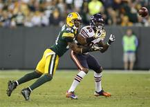 Green Bay Packers cornerback Charles Woodson (L) intercepts the ball against Chicago Bears wide receiver Earl Bennett (80) in the second half during their NFL football game in Green Bay, Wisconsin September 13, 2012. REUTERS/Darren Hauck