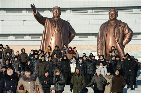 North Korean people visit in front of bronze statues of North Korea founder Kim Il-sung (L) and late leader Kim Jong-il at Mansudae in Pyongyang, in this photo taken by Kyodo February 15, 2013, a day before the birthday of their late leader, Kim Jong-il. REUTERS/Kyodo