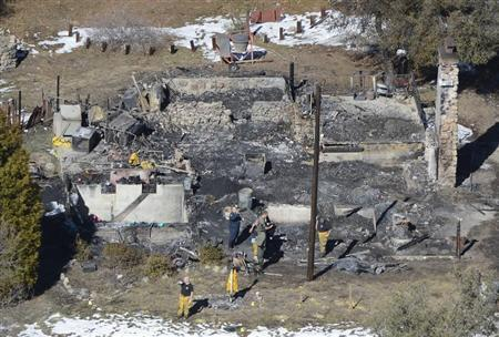 Authorities stand at the site of a burnt out cabin near Angelus Oaks, California February 13, 2013, where police believe they engaged in a shootout with fugitive former Los Angeles police officer Christopher Dorner on Tuesday. REUTERS/Gene Blevins