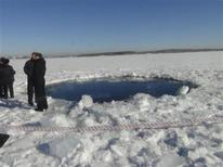 Miles de trabajadores rusos de emergencia salieron el sábado a limpiar los daños ocasionados por un meteorito que explotó en los montes Urales, dañando edificios, reventando ventanas y provocando una lluvia de cristales rotos sobre las personas. En la imagen, de 15 de febrero, la policía rusa trabaja cerca del agujero de hielo en la región de Chelyabinsk, punto de impacto del meteorito visto en la región de los Urales. REUTERS/Chelyabinsk region Interior Ministry/Handout