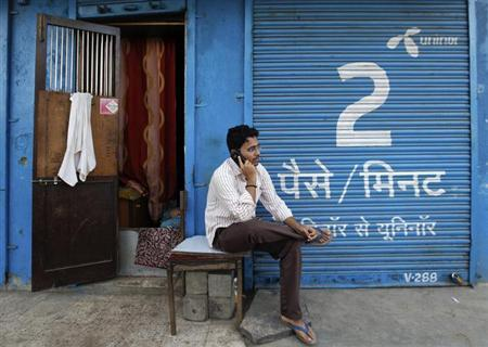A man speaks on a mobile phone in front of a closed shop displaying an advertisement for Uninor on its shutters in Mumbai February 6, 2012. REUTERS/Danish Siddiqui