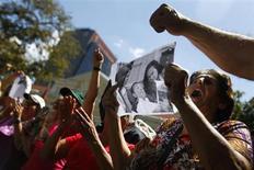 Partidários de Hugo Chávez levantam cópia da fotografia do líder divulgada pelo governo na praça Bolívar em Caracas, Venezuela. 15/02/2013 REUTERS/Carlos Garcia Rawlins