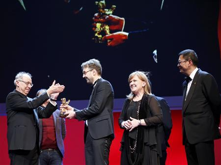 Festival director Dieter Kosslick (L) applauds as jury president Wong Kar Wai (R) watches as director Calin Peter Netzer and producer Ada Solomon recieve the Golden Bear award for Best Film for their movie ''Pozitia Copilului'' (Child's Pose) during the awards ceremony at the 63rd Berlinale International Film Festival in Berlin February 16, 2013. REUTERS/Fabrizio Bensch (GERMANY - Tags: ENTERTAINMENT)