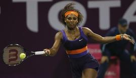 Serena Williams of the U.S. returns the ball to Maria Sharapova of Russia during their women's semi-final match at the Qatar Open tennis tournament in Doha February 16, 2013. REUTERS/Fadi Al-Assaad