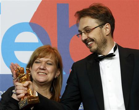 Director Calin Peter Netzer and producer Ada Solomon look at the Golden Bear award received for the Best Film for ''Pozitia Copilului'' (Child's Pose) at the 63rd Berlinale International Film Festival in Berlin February 16, 2013. REUTERS/Tobias Schwarz (GERMANY - Tags: ENTERTAINMENT)