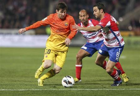 Barcelona's Lionel Messi (L) controls the ball against Granada's Inigo Lopez (R) and Mikel Rico during their Spanish first division soccer match at Los Carmenes stadium in Granada February 16, 2013.REUTERS/Pepe Marin