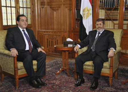 Egyptian President Mohamed Morsi (R) meets with opposition figure Ayman Nour (L), chairman of el-Ghad political party, in Cairo February 16, 2013. REUTERS/Egyptian Presidency/Handout