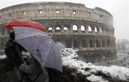 Tourists protect themselves from the falling snow with umbrellas as they view Rome's ancient Colosseum February 3, 2012. REUTERS/Alessandro Bianchi