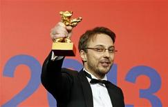 "Director Calin Peter Netzer holds the Golden Bear award for the Best Film received for the movie ""Pozitia Copilului"" (Child's Pose) at the 63rd Berlinale International Film Festival in Berlin February 16, 2013. REUTERS/Tobias Schwarz"
