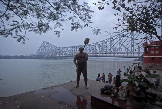 A wrestler does warm up exercises near a permanent mud wrestling ring at 'Sia Ram bhajan samati akhaara', a traditional wrestling training centre, on the banks of the river Ganges in Kolkata February 17, 2013. Government will seek the support of other countries where wrestling is popular to help the sport remain an Olympic discipline, India's sports minister said on Wednesday. Wrestlers fought friendly matches at the training centre on Sunday to support the movement to reinstate wrestling as an Olympic sport, a senior wrestler and trainer said. REUTERS/Rupak De Chowdhuri