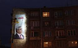 """A worker removes an election poster of Armenia's current President Serzh Sarksyan in Yerevan, February 16, 2013. Armenia's presidential elections will be held on February 18. The poster is being taken down for the """"day of silence"""" on February 17 where political campaigning is not allowed. REUTERS/David Mdzinarishvili"""